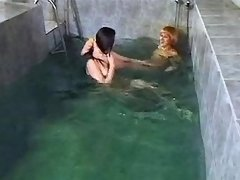 Two lezzies play with pussy in pool